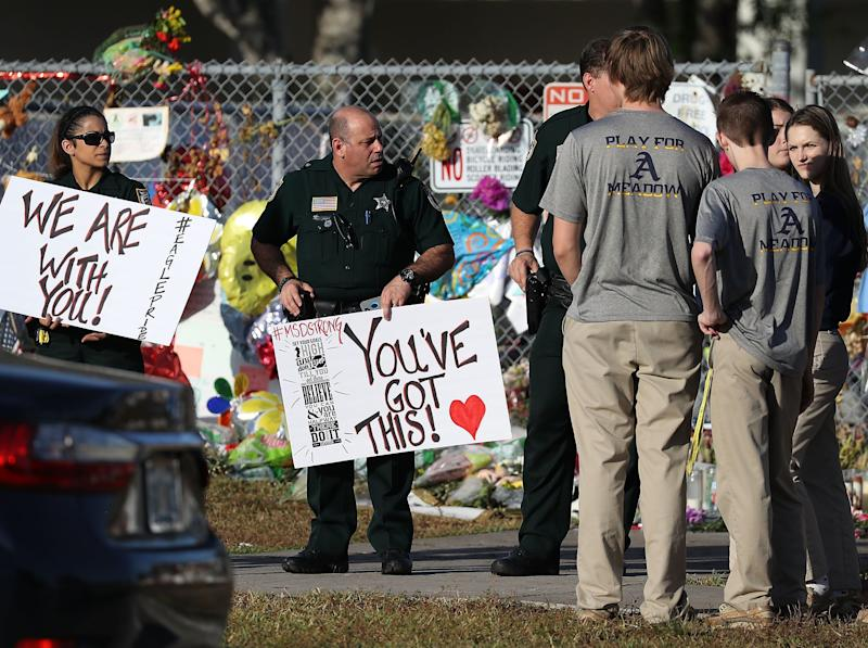 Police officers from Broward County welcome students as they arrive at Marjory Stoneman Douglas High School for their first day of classes after a deadly mass shooting at the school.