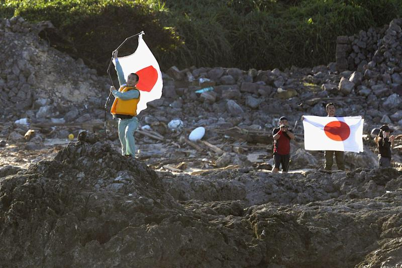 FILE - In this Aug. 19, 2012 file photo, Japanese activists hold the national flags on Uotsuri island, one of the islands of Senkaku in Japanese and Diaoyu in Chinese, in East China Sea. An unauthorized landing by Japanese activists on an island at the center of a dispute with China is sparking nationalist outrage and fueling calls on both sides for aggressive government action that some fear could lead to an escalation of tensions. Japanese authorities on Monday, Aug. 20, 2012, questioned the 10 Japanese, including five local assembly members, who swam ashore on the disputed island the day before. (AP Photo/Kyodo News, File) JAPAN OUT, MANDATORY CREDIT, NO LICENSING IN CHINA, HONG KONG, JAPAN, SOUTH KOREA AND FRANCE