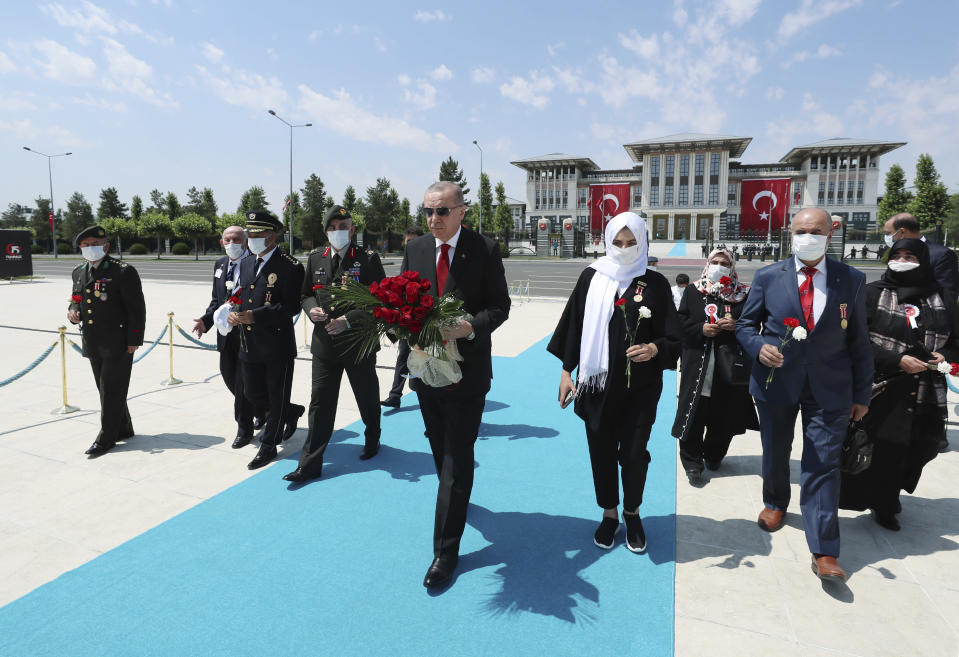 """Turkey's President Recep Tayyip Erdogan and family members of coup victims walk to place a floral tribute at the """"Martyrs Monument"""" outside his presidential palace, in Ankara, Turkey, Wednesday, July 15, 2020. Turkey is marking the fourth anniversary of the July 15 failed coup attempt against the government, with prayers and other events remembering its victims. (Turkish Presidency via AP, Pool)"""