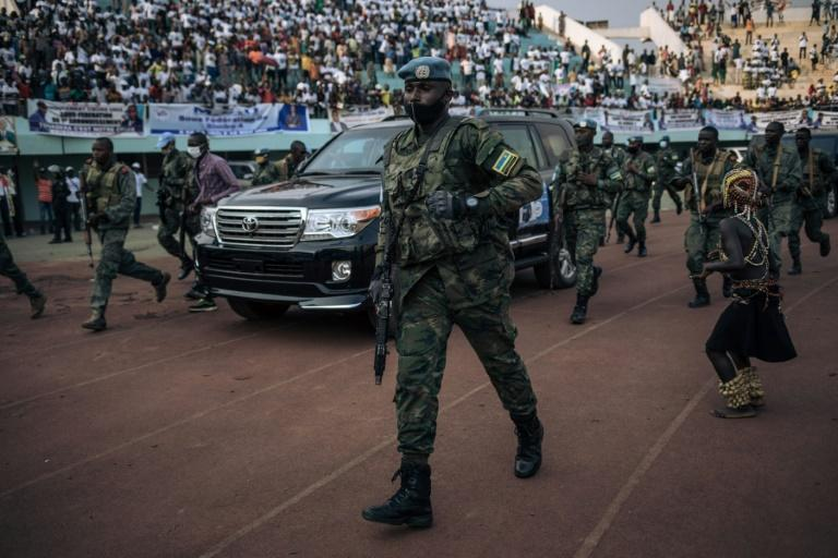 President Faustin-Archange Touadera'S motorcade arrives for an electoral rally escorted by the presidential guard, Russian mercenaries, and Rwandan UN peacekeepers
