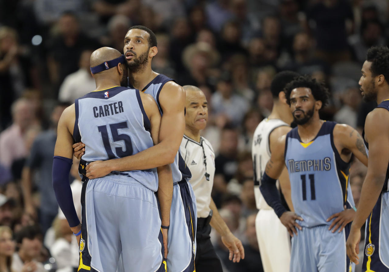 Memphis Grizzlies guard Vince Carter (15) is held by teammate Brandan Wright (34) after he was called for a technical foul during the first half in Game 2 of a first-round NBA basketball playoff series against the San Antonio Spurs, Monday, April 17, 2017, in San Antonio. (AP Photo/Eric Gay)