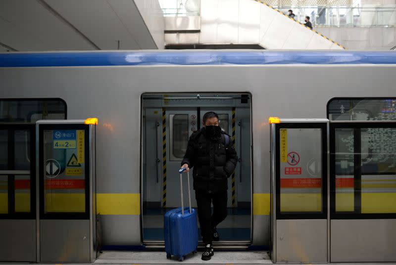 FILE PHOTO: Man wearing a face mask walks out of the subway with a suitcase in the morning after the extended Lunar New Year holiday caused by the novel coronavirus outbreak, at the Xierqi subway station, in Beijing