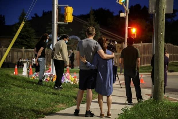 People and members of the media are seen at a makeshift memorial at the fatal crime scene where a man driving a pickup truck jumped the curb and ran over a Muslim family in what police say was a deliberately targeted anti-Islamic hate crime, in London, Ont., on Monday.