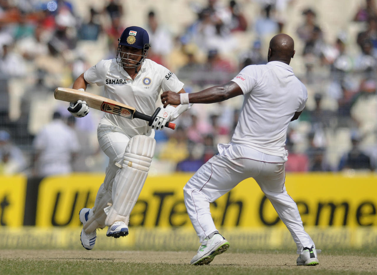 Tino Best of West Indies avoids a collusion with Sachin Tendulkar of India as the latter runs to complete a run during day two of the first Star Sports test match between India and The West Indies held at The Eden Gardens Stadium in Kolkata, India on the 7th November 2013 (BCCI)