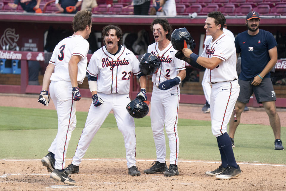 Virginia's Kyle Teel (3) steps on home plate after hitting a grand slam as Jake Gelof (22), Max Cotier (2), and Zack Gelof, front right, celebrate during an NCAA college baseball tournament super regional game against Dallas Baptist, Monday, June 14, 2021, in Columbia, S.C. (AP Photo/Sean Rayford)