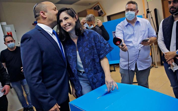 Bennett kisses his wife Gilat as she casts her vote at a polling station in the Israeli city of Raanana on March 23 - AFP