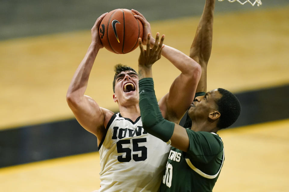 FILE - Iowa center Luka Garza (55) drives to the basket against Michigan State forward Marcus Bingham Jr., right, during the second half of an NCAA college basketball game in Iowa City, Iowa, in this Tuesday, Feb. 2, 2021, file photo. Garza was named The Associated Press men's basketball player of the year on Thursday, April 1. (AP Photo/Charlie Neibergall, File)