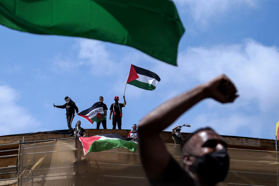 Demonstrators holding flags stand on the top of a building during a protest outside Israeli Consulate against Israel and in support of Palestinians, Saturday, May 15, 2021 in the Westwood section of Los Angeles. (AP Photo/Ringo H.W. Chiu)