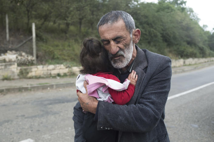A local resident holds his granddaughter in the Hadrut province of self-proclaimed Republic of Nagorno-Karabakh, Azerbaijan, Thursday, Oct. 1, 2020. Two French and two Armenian journalists have been injured in the South Caucasus separatist region of Nagorno-Karabakh, where heavy fighting between Armenian and Azerbaijani forces this week marked the biggest escalation in years of a decades-old conflict. (Karo Sahakyan/ArmGov PAN Photo via AP)