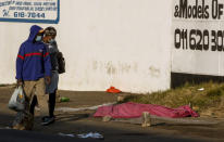 A couple walks past a body covered with a blanket after protests in the area, in Johannesburg, South Africa, Sunday, July 11, 2021. Protests have spread from the KwaZulu Natal province to Johannesburg against the imprisonment of former South African President Jacob Zuma who was imprisoned last week for contempt of court. (AP Photo/Themba Hadebe)
