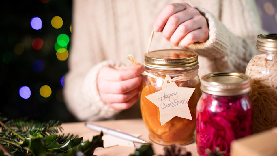 Putting Reusable Wooden Gift Tag On Homemade Jars Of Preserved Fruit For Eco Friendly Christmas Gift.