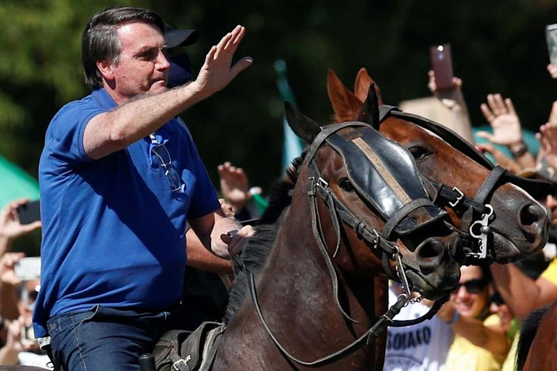 Brazil's President Jair Bolsonaro rides a horse during a meeting with supporters protesting in his favour: REUTERS