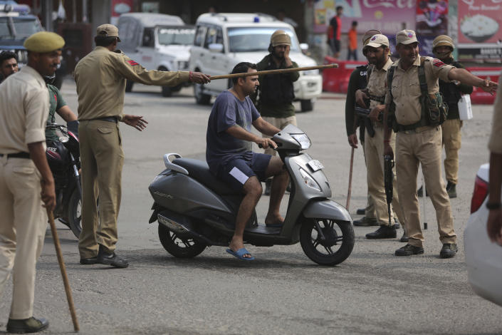 """Indian police check the identity of commuters in Jammu, India, Tuesday, Aug.6, 2019. India's lower house of Parliament was set to ratify a bill Tuesday that would downgrade the governance of India-administered, Muslim-majority Kashmir amid an indefinite security lockdown in the disputed Himalayan region. The Hindu nationalist-led government of Prime Minister Narendra Modi moved the """"Jammu and Kashmir Reorganization Bill"""" for a vote by the Lok Sahba a day after the measure was introduced alongside a presidential order dissolving a constitutional provision that gave Kashmiris exclusive, hereditary rights. (AP Photo/Channi Anand)"""