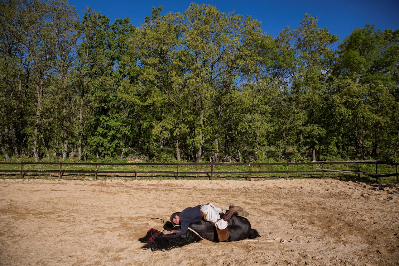 """Fernando Noailles, emotional therapist, lays on top of his horse named Madrid in Guadalix de la Sierra, outside Madrid, Spain, May 31, 2016. Noailles uses his animals to help people suffering from stress and anxiety. REUTERS/Juan Medina  SEARCH """"MEDINA HORSES"""" FOR THIS STORY. SEARCH """"WIDER IMAGE"""" FOR ALL STORIES.  TPX IMAGES OF THE DAY."""