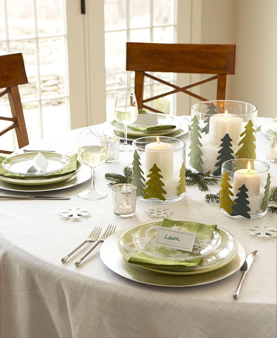 """<p>Transform your table into an enchanted pine forest. Just cut out fir shapes from felt and hot-glue them onto candle holders filled with faux snow. </p><p><a class=""""link rapid-noclick-resp"""" href=""""https://www.amazon.com/flic-flac-inches-Assorted-Fabric-Patchwork/dp/B01GCRXBVE?tag=syn-yahoo-20&ascsubtag=%5Bartid%7C10055.g.2196%5Bsrc%7Cyahoo-us"""" rel=""""nofollow noopener"""" target=""""_blank"""" data-ylk=""""slk:SHOP FELT"""">SHOP FELT</a></p><p><em><a href=""""https://www.goodhousekeeping.com/holidays/christmas-ideas/how-to/a19080/felt-christmas-tree-topped-hurricanes/"""" rel=""""nofollow noopener"""" target=""""_blank"""" data-ylk=""""slk:Get the tutorial »"""" class=""""link rapid-noclick-resp"""">Get the tutorial »</a></em><br></p>"""