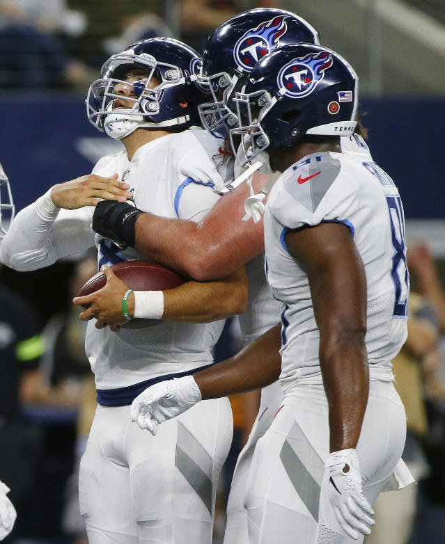 Tennessee Titans quarterback Marcus Mariota, left, celebrates his touchdown run with team mates during the second half of an NFL football game against the Dallas Cowboys, Monday, Nov. 5, 2018, in Arlington, Texas. (AP Photo/Michael Ainsworth)