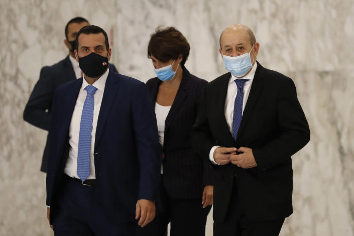 """French Foreign Minister Jean-Yves Le Drian, right, leaves the Presidential Palace after his meeting with Lebanese President Michel Aoun in Baabda, east of Beirut, Lebanon, Thursday, May 6, 2021. Le Drian began a visit to Lebanon Thursday with a message of """"great firmness"""" to its political leaders, threatening to take additional measures against officials obstructing the formation of a government in the crisis-hit country. (AP Photo/Hussein Malla)"""