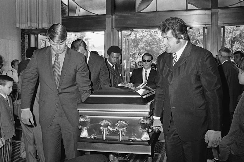 Chicago Bears teammates of Brian Piccolo, who became too ill to play in the middle of last season, carry his coffin into Christ the King Church for funeral services in Chicago, on Friday, June 19, 1970. Left, front to back, are Randy Jackson, Dick Butkus, and Gale Sayers, Picoolo's roommate. Right, Ed O'Bradovich. (AP Photo)