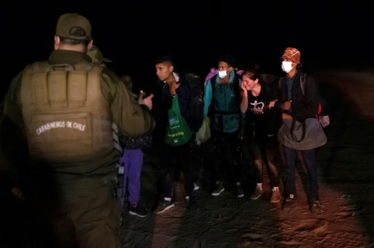 Venezuelan migrants being arrested by Chilean police at the border with Peru (AFP/MARTIN BERNETTI)