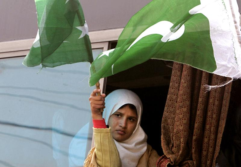 A girl holds Pakistani flags during a rally lead by the Pakistani Sunni Muslim cleric Tahir-ul-Qadri, unseen, as they march towards Islamabad, in Lahore, Pakistan, Sunday, Jan. 13, 2013. After years in Canada, Qadri returned to Pakistan last month and gave a speech demanding that sweeping election reforms be implemented before elections expected to take place this spring. On Thursday, Pakistan's Minister of Interior Rehman Malik issued a strongly worded statement that Qadri would not be allowed to rally in Islamabad, warning that the Taliban might attack the event. (AP Photo/K.M. Chaudary)