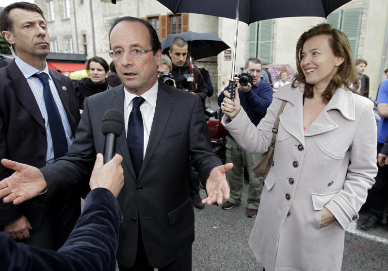 French Socialist Party candidate for the french presidential election Francois Hollande with his companion French journalist Valerie Trierweiler, answer  journalist's questions during a visit at the market in Tulle, southwestern France, on the eve of the presidential election second round, Saturday, May 5, 2012.(AP Photo/Lionel Cironneau)