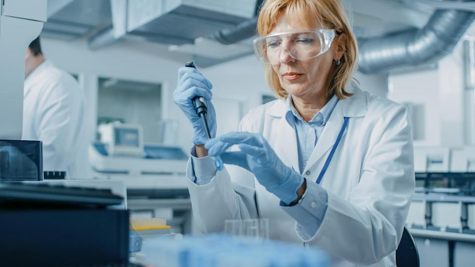 Female Research Scientist Uses Micro Pipette while Working with Test Tubes.