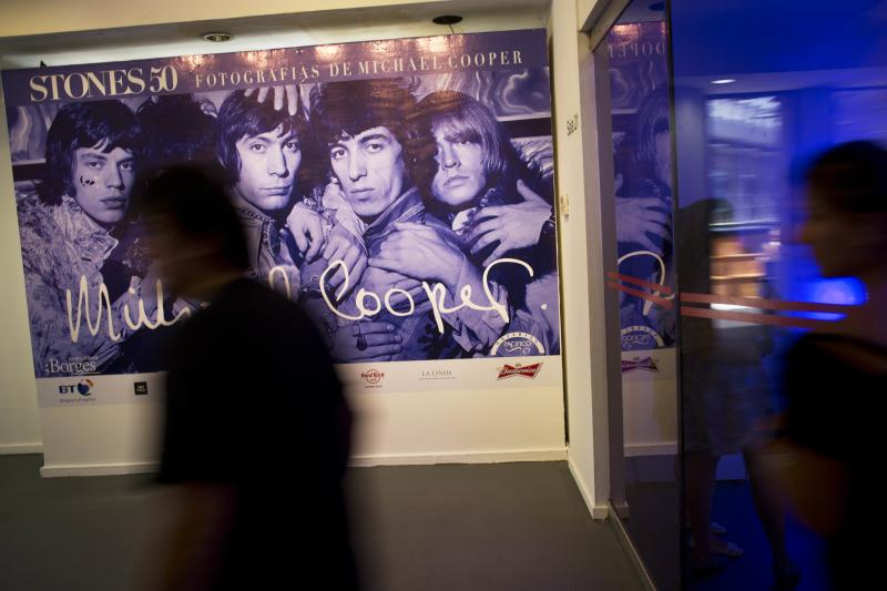 A man walks past a banner featuring a Michael Cooper photo of the Rolling Stones, on the eve of the inauguration of Stones 50, an exhibit of Cooper's photos, the official photographer of the Rolling Stones in the first years of the band, presented by his son Adam, at the Centro Cultural Borges in Buenos Aires, Argentina, Thursday, Dec. 12, 2013. (AP Photo/Rodrigo Abd)