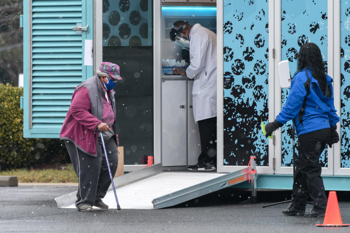 In this Thursday, Feb. 11, 2021, photo a woman arrives at a COVID-19 vaccination clinic outside the Pennsylvania Avenue Baptist Church, Thursday, Feb. 11, 2021, in southeast Washington. (AP Photo/Jacquelyn Martin)