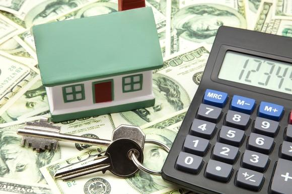 Toy house, calculator, and keys sitting on a flat surface on top of spread-out money.