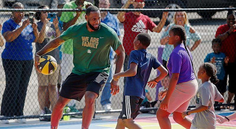 LeBron James is triple-teamed by I Promise School students during a pickup game of basketball during the debut of the new basketball court at the school Aug. 14 in Akron, Ohio.