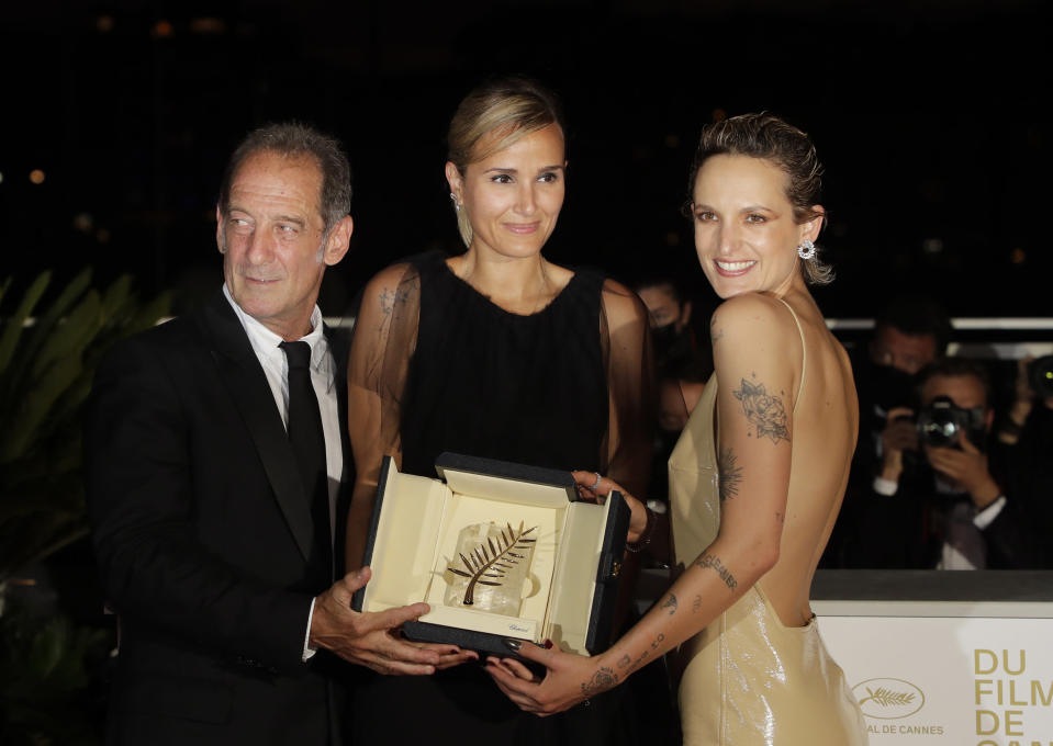Director Julia Ducournau, center, winner of the Palme d'Or for the film 'Titane' poses with Vincent Lindon, left, and Agathe Rousselle during a photo call following the awards ceremony at the 74th international film festival, Cannes, southern France, Saturday, July 17, 2021. (Photo by Vianney Le Caer/Invision/AP)