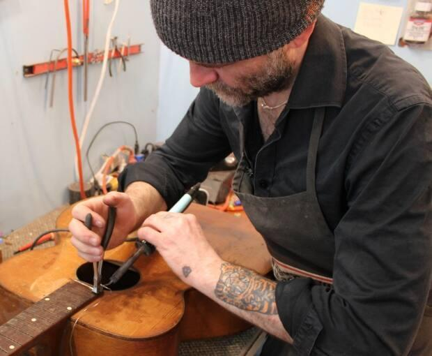 Chris Kearsey removes worn guitar frets using a soldering iron and pliers.