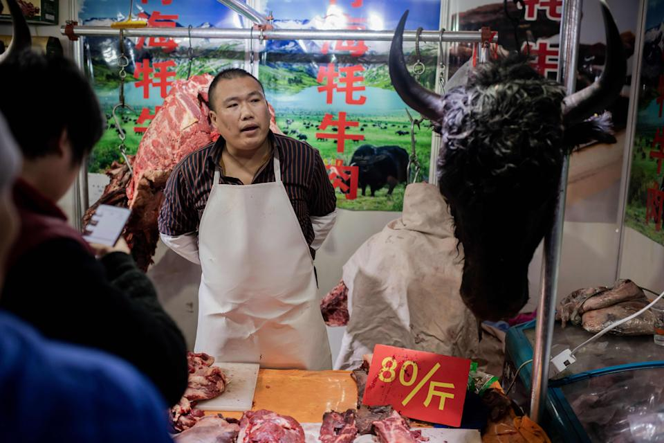 """This picture taken on January 15, 2020 shows a butcher (C) selling yak meat at a market in Beijing. - The World Health Organisation (WHO) said on January 20 it believed an animal source was the """"primary source"""" of the outbreak, and authorities in the central Chinese city of Wuhan identified a seafood market in their city as the centre of the epidemic, but China has since confirmed that there was evidence the virus is now passing from person to person, without any contact with the now-closed market. (Photo by NICOLAS ASFOURI / AFP) (Photo by NICOLAS ASFOURI/AFP via Getty Images)"""