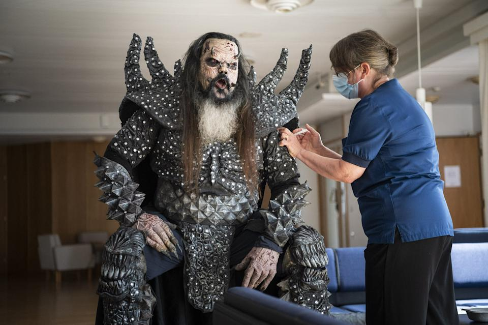 A health care working wearing a face mask gives an injection into the arm of Petteri Putaansuu, better known as Mr Lordi of the Finnish hard rock band Lordi, wearking full costume.