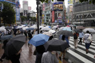 Morning commuters with umbrella cover a crosswalk Tuesday, July 27, 2021, in Tokyo. The rains have come to Tokyo and its Olympics. After many days of blistering sunshine, the rain cooled Tokyo by about 10 degrees and took the edge off. But worries about the effect of Tropical Storm Nepartak have led to changes in events and some cancellations of practices as preparations proceed. The storm is expected to make landfall in Japan on Tuesday evening. (AP Photo/Kiichiro Sato)