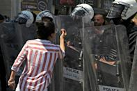 A protester confronts Palestinian security forces during a demonstration calling for Palestinian president Mahmud Abbas to quit after Nizar Banat, a critic of the Palestinian Authority, died following his arrest in the occupied West Bank
