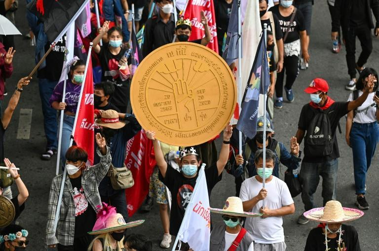 A protester holds a replica of a plaque from Thailand's 1932 Siamese Revolution as marchers commemorate the anniversary of the event in Bangkok