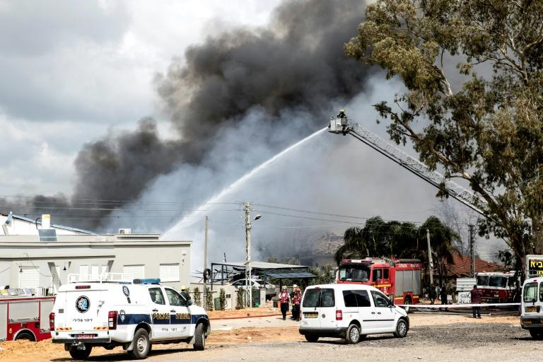Israeli firefighters douse flames after a fire at a fireworks warehouse in Porat village killed at two people on March 14, 2017