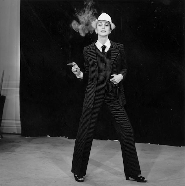 "A model wearing a pinstriped trouser suit by Yves Saint Laurent. His plainer suit for evening wear known as ""Le Smoking"" became a signature piece. (Photo: Reg Lancaster/Getty Images)"