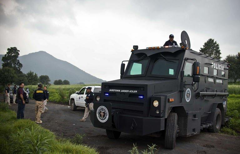Mexican police officers block a road leading to a park in the municipality of Tlalmanalco, some 30 km southeast of Mexico City on August 22, 2013, where at least 7 bodies were discovered in a mass grave