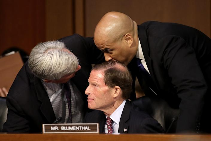 Left to right: Sens. Sheldon Whitehouse, D-R.I., Richard Blumenthal, D-Conn. and Cory Booker, D-N.J. huddle as Supreme Court nominee Judge Brett Kavanaugh appears for his confirmation hearing before the Senate Judiciary Committee in the Hart Senate Office Building on Capitol Hill Tuesday in Washington, D.C. (Photo: Mark Wilson/Getty Images)