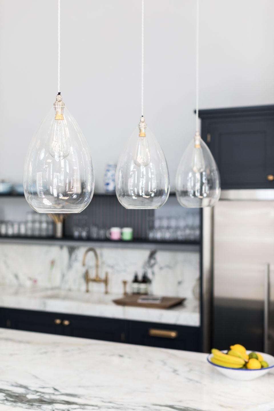 """<p>From small pendants to statement shades, there are lots of ways to brighten up your kitchen island. If it's a space where you'll be preparing food then opt for bright task lighting, however if you're dreaming of creating a spot to unwind then consider something softer. </p><p>'Pendant lighting is an elegant addition that will bring an extra layer of interest to the kitchen's design,' says Graeme. 'The low hanging bulbs will offer extra light for everyday tasks without overwhelming the space.' </p><p>• Clear glass pendant, £215 from <a href=""""https://www.fritzfryer.co.uk/products/wellington-clear-glass-pendant-light/"""" rel=""""nofollow noopener"""" target=""""_blank"""" data-ylk=""""slk:Fritz Fryer"""" class=""""link rapid-noclick-resp"""">Fritz Fryer </a></p><p><strong>READ MORE</strong>: <a href=""""https://www.housebeautiful.com/uk/decorate/kitchen/a31990026/kitchen-lighting-ideas/"""" rel=""""nofollow noopener"""" target=""""_blank"""" data-ylk=""""slk:Kitchen lighting ideas for the hardest-working room in your house"""" class=""""link rapid-noclick-resp"""">Kitchen lighting ideas for the hardest-working room in your house</a></p>"""