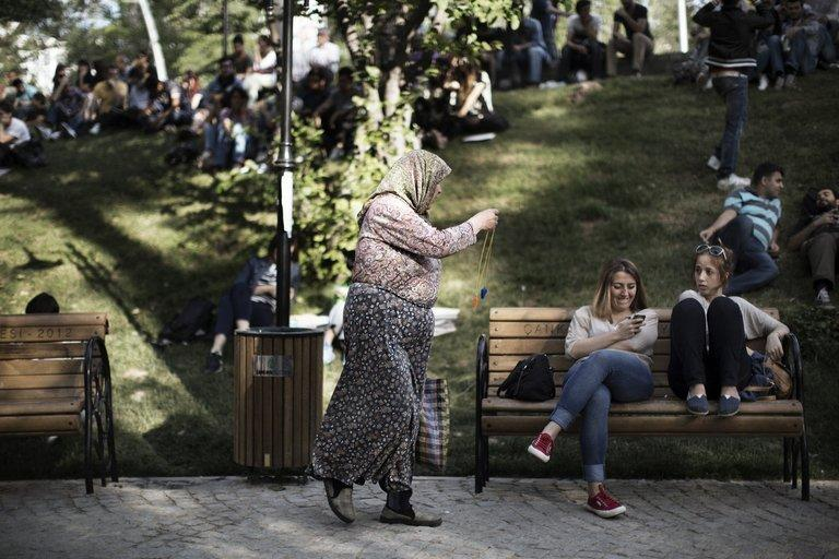 A traditionally-veiled Turkish woman sells whistles to young activists sitting at Kugulu Park in Ankara on June 7, 2013