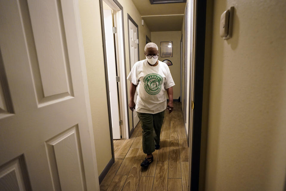 Doris Brown walks down the hallway of her home Friday, July 31, 2020, in Houston. Brown's home flooded during Harvey and she's part of a group called the Harvey Forgotten Survivors Caucus. (AP Photo/David J. Phillip)