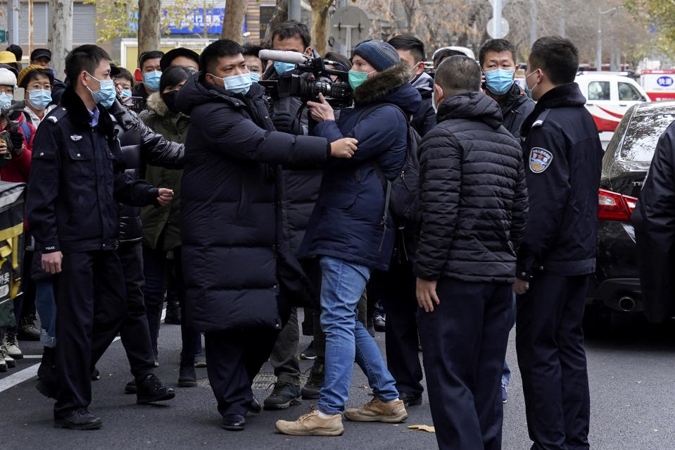 "Foreign journalists are stopped by Chinese policemen as they try to film supporters of Zhou Xiaoxuan outside a courthouse in Beijing, Wednesday, Dec. 2, 2020. The Chinese woman who filed a sexual harassment lawsuit against a TV host told cheering supporters at a courthouse Wednesday she hopes her case encourages other ""victims of gender violence"" in a system that gives them few options to pursue complaints.(AP Photo/Andy Wong)"