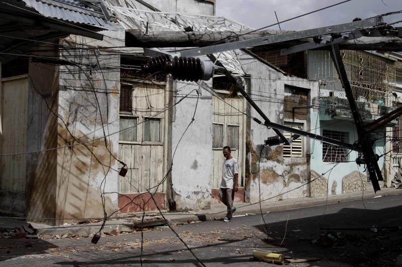 A man walks along a street where electrical lines hang damaged by Hurricane Sandy in Santiago de Cuba, Cuba, Friday Oct. 26, 2012. Sandy was a Category 2 hurricane when it wreaked havoc in Cuba on Thursday, killing 11 people in eastern Santiago and Guantanamo provinces as its winds and rain destroyed thousands of houses and ripped off roofs. (AP Photo/Franklin Reyes)