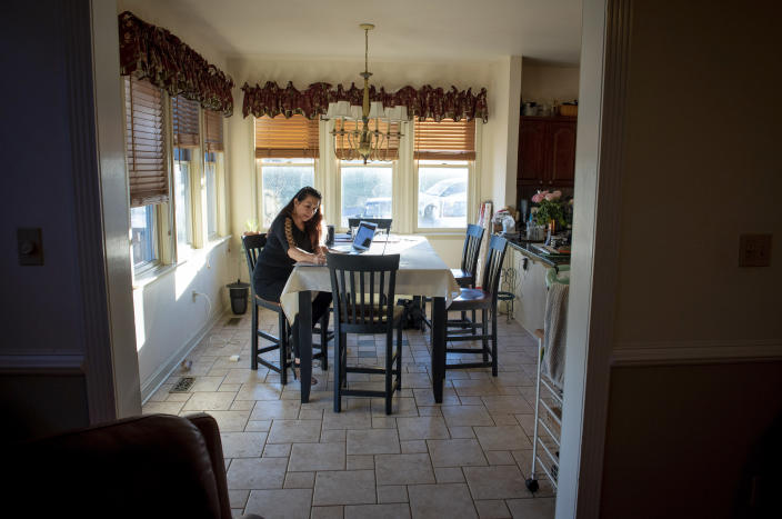 """Natalie Abbas sits at her dining room table, her """"Command Post,"""" in Myersville, Md., Tuesday, Jan. 19, 2021, the day before the presidential inauguration. As a member of Braver Angels, Abbas, who believes the election was stolen, meets regularly with a neighbor who cheers Biden as the rightful winner, to ponder the greatest challenge facing Biden and American society: how can they find common ground if they no longer exist in the same reality? (AP Photo/Cliff Owen)"""