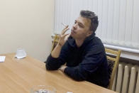 FILE - In this handout file photo released by ONT channel on Wednesday, June 2, 2021, dissident journalist Raman Pratasevich smokes a cigarette while speaking in a video from a detention center in Minsk, Belarus. The footage of Raman Pratasevich was part of an hour-long TV program aired late Wednesday by the state-controlled ONT channel. Political prisoners in Belarus are coming under increasing pressure following the recent arrest of activist Raman Pratasevich from a forcibly diverted Ryanair flight. Human rights groups say these prisoners have been marked with yellow tags sewn into their prison uniforms to single them out from regular prisoners. (ONT channel VIA AP, File)