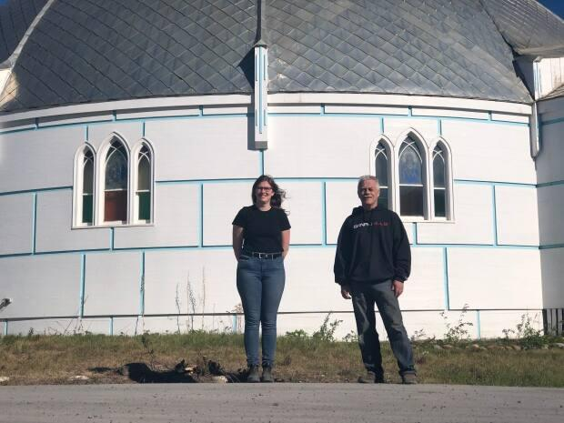 Permafrost scientist Alice Wilson and Project Uplift coordinator Peter Clarkson stand in front of Inuvik's Our Lady of Victory Catholic Church, better known as the igloo church. Its floor began dropping a couple of years ago as a result of the freeze-thaw cycle of permafrost the church is built on. (Mackenzie Scott/CBC - image credit)