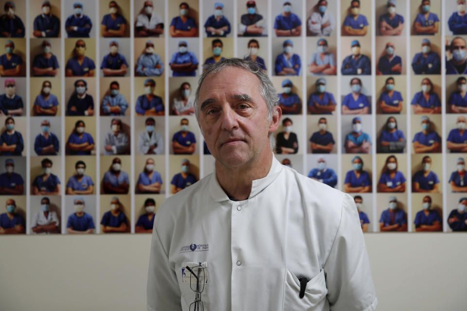 Dr. Philippe Montravers poses in front of a collection of portraits of medical staff at Bichat Hospital, AP-HP, in Paris, Wednesday, Dec. 2, 2020. One of the biggest hospitals in Paris, Bichat Hospital, this month reopened all 22 of its operating rooms. It is once again performing surgeries that were stopped during virus surges that pushed France's death toll past 55,000. (AP Photo/Francois Mori)